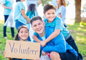 "Handsome mid adult Hispanic father and his preteen daughte and elementary age son smiles while holding a ""Volunteer' sign. They are helping their neighbors clean up their community. People are in the background."
